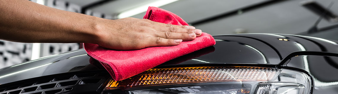 Automotive specialist detailing vehicle with hand cloth