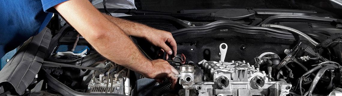 Automotive service technician repairing vehicle engine